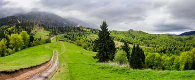 Gorgeous countryside of Carpathian mountains. Beautiful springtime scenery on a cloudy day. country road runs down the grassy hillside Stock Photography