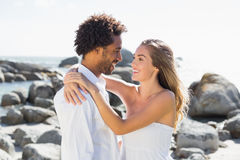 Gorgeous couple embracing by the coast Stock Photo