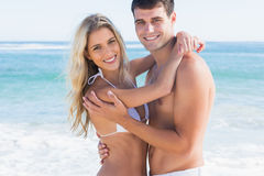 Gorgeous couple hugging and smiling at camera. At the beach Stock Image