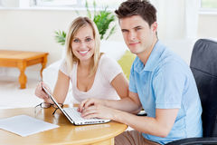 Gorgeous couple working together on the laptop Stock Photos