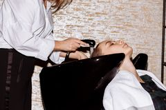 Gorgeous cute young woman enjoying head massage while professional hairdresser applying shampoo her hair. Close up of hairdresser stock photos