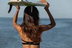 Gorgeous dark-haired girl in a black bra holds a surfboard over her head near the sea. Back view. stock photography