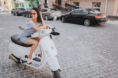 Gorgeous dark-haired girl is sitting on motorcycle and leaning on it. She is holding one hand close to the head. She is Royalty Free Stock Photos