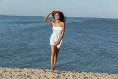 Gorgeous dark-haired girl in white dress, hat and sunglasses walk on the sandy beach near the sea on a sunny day. stock photo