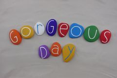 Gorgeous day, celebration of a beautiful day with colored stones over white sand royalty free stock photos