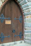 Gorgeous detail in old wood doors of stone church Royalty Free Stock Image