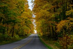 Fall road in Pictured Rocks National Lakeshore, Munising, MI, US. Gorgeous display of fall colors, leaves, red, orange, green and yellow trees with both side of Royalty Free Stock Image