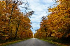 Fall road in Pictured Rocks National Lakeshore, Munising, MI, US. Gorgeous display of fall colors, leaves, red, orange, green and yellow trees with both side of Stock Photography