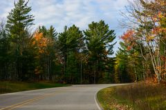 Fall road in Pictured Rocks National Lakeshore, Munising, MI, US. Gorgeous display of fall colors, leaves, red, orange, green and yellow trees with both side of Stock Images