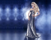 Gorgeous elegant blonde lady posing in fashionable silver dress. Beautiful young blonde woman posing in fashionable silver evening dress over the dark interior Stock Images