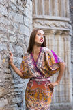 Gorgeous elegant girl in ethnic dress leaning on an antique wall Stock Photography