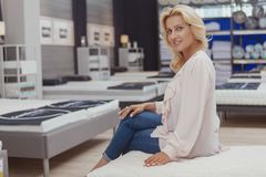 Gorgeous elegant mature woman shopping for new orthopedic bed. Charming mature woman smiling to the camera sitting on a new orthopedic bed at furniture store royalty free stock images