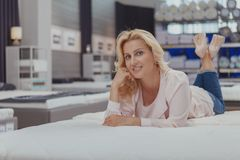 Gorgeous elegant mature woman shopping for new orthopedic bed. Relaxation, real estate concept. Beautiful cheerful blond haired woman smiling to the camera royalty free stock photos