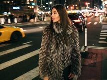 Gorgeous elegant woman walking on night city street wearing fake fur jacket and holding bag looking to the side. royalty free stock images