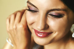 Gorgeous emotional smiling exotic bride putting on earrings clos Stock Photography