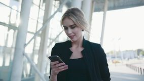 Gorgeous European businesswoman with formal hairstyle in a hurry passes the airport terminal, texts the message on her. Phone, looks around. Fashionable outfit stock video footage