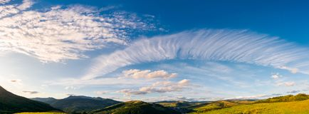 Gorgeous evening clouds over the mountains. Lovely panorama of striking cloudscape on a blue sky Stock Photography