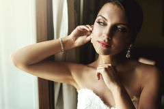Gorgeous exotic french bride in white dress posing near window c Stock Images