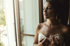Gorgeous exotic french bride in white dress posing near window c Royalty Free Stock Image