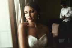 Gorgeous exotic french bride in white dress posing near window w Stock Photos