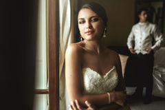 Gorgeous exotic french bride in white dress posing near window w Stock Photography