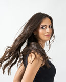 Gorgeous exotic tanned beauty with frozen motion of her long flowing hair. Portrait over gray studio background Royalty Free Stock Photo
