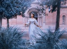 Gorgeous fairy-tale princess in light white dress with open bare shoulders and full sleeves runs away from castle, girl. With dark collected hair and wonderful royalty free stock images