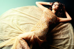 Gorgeous. Fashion shot of a stunning woman in luxurious golden dress Stock Photo