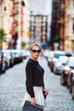 Gorgeous fashionable woman crossing city street and carrying shopping bags. Concept photo of New York City shopping Royalty Free Stock Images