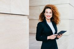 Gorgeous female in black suit, having curly bushy hair, blue eyes and red painted lips smiling pleasantly while typing text messag. E on tablet. Successful royalty free stock photos