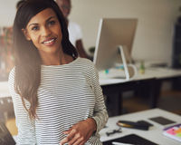 Gorgeous female business owner. Single gorgeous female business owner wearing black and white striped blouse with partner on computer in background Stock Photo