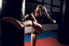 Female fighter hitting heavy bag with her leg. Gorgeous female fighter with blonde hair pulled back in long braid, dressed in black crop top and camouflage Royalty Free Stock Photo