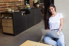 Gorgeous female freelancer using net-book for distance job while sitting in modern coffee shop Stock Photos