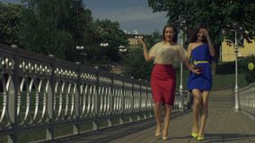 Gorgeous female friends enjoying leisure in the city. Attractive stylish women enjoying leisure and talking while strolling on old pedestrian bridge over stock video