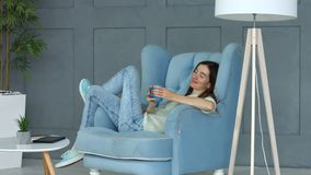 Positive woman enjoying morning coffee in armchair stock footage