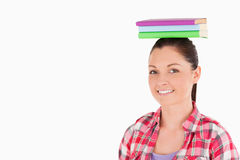 Gorgeous female holding books on her head Royalty Free Stock Photography