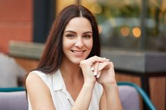 Gorgeous female lady has gentle smile, has dark hair, wears blouse, looks directly into camera, being in good mood as spends free. Time with friends at coffee Royalty Free Stock Images