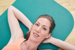 Gorgeous female lying on gym floor Royalty Free Stock Images