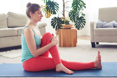 Gorgeous female meditating and starching muscles on yoga mat Royalty Free Stock Photography