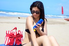Gorgeous female model putting sun cream on her body on tropical beach Royalty Free Stock Photos