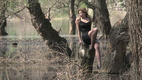 Gorgeous Female Model Sitting On Stump At Flooded. In the frame there is a young sexy female model in mini dress posing for the camera sitting on a high stump in stock video footage
