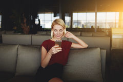 Gorgeous Female Reading News Via Network On Mobile Phone While Waiting For Her Order In Modern Coffee Shop, Royalty Free Stock Photography
