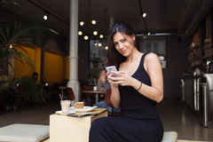Gorgeous female student hold telephone and looking at you while relaxing in sidewalk cafe after lectures Royalty Free Stock Photos