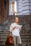 Gorgeous female tourist with a map discovering a foreign city Stock Photography