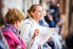 Gorgeous female tourist with a map discovering a foreign city Royalty Free Stock Photography
