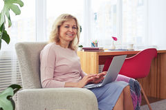 Gorgeous female working in laptop while sitting in armchair Royalty Free Stock Image