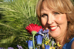 Gorgeous fifty year old woman. With flowers Royalty Free Stock Photo