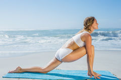 Gorgeous fit blonde in lunging yoga pose on the beach Stock Photo