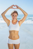 Gorgeous fit blonde making heart shape with hands by the sea Royalty Free Stock Photography