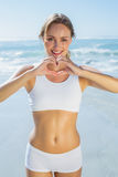 Gorgeous fit blonde making heart shape with hands by the sea Stock Photos